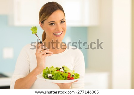 pretty woman eating vegetable salad in home kitchen