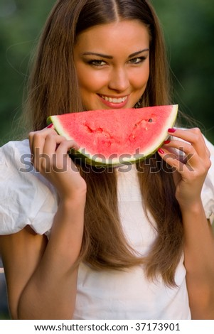 Pretty woman eating water-melon outdoor - stock photo