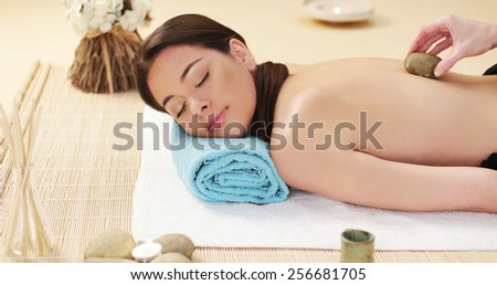 Pretty woman enjoying a lava stone massage with hot rocks in a spa treatment lying on her stomach on a mat with her eyes close in bliss and a serene expression - stock photo