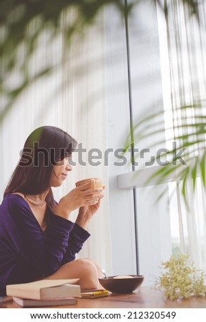 Pretty woman enjoying coffee and looking out of the window - stock photo