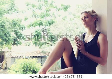 Pretty woman enjoying her morning coffee on a veranda - stock photo