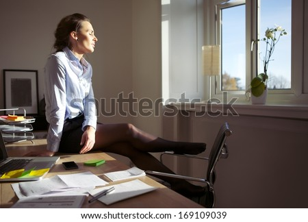 Pretty woman enjoying the sun. Businesswoman sitting on desk with her eyes closed relaxing in sunlight. Caucasian female model in office. - stock photo