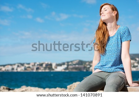 Pretty woman enjoying the sunshine while sitting on a wooden rail at the coast overlooking the ocean - stock photo