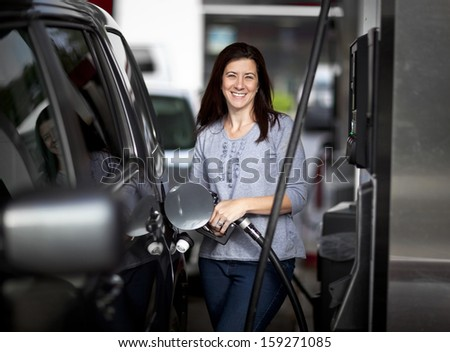 Pretty woman filling her car with petrol at gas statiion - stock photo