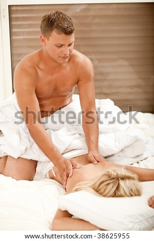 Pretty woman getting massage from handsome young male - stock photo
