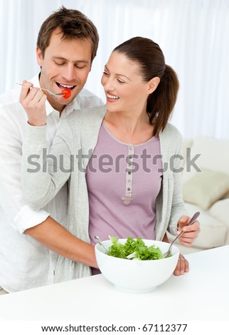Pretty woman giving a tomato to his boyfriend while preparing a salad in the kitchen - stock photo