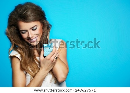 Pretty woman hands a gift box, isolated on blue - stock photo