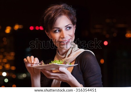 Pretty woman having dinner at night in outdoors restaurant, eating fresh green salad, healthy nutrition, with pleasure spending evening on the party - stock photo