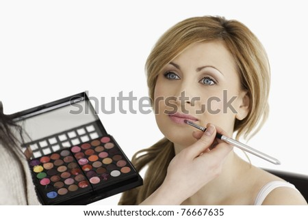 Pretty woman having her make up done by a make up artist in a studio