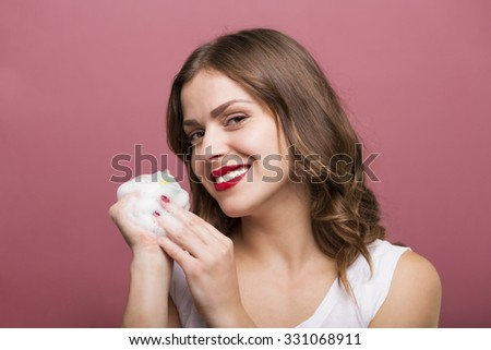Pretty woman holding a bottle of lotion and a bubble maker - stock photo