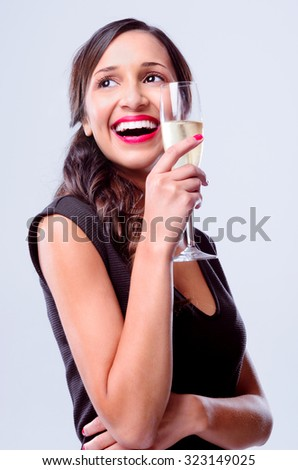 Pretty woman holding a glass of champagne looking away, wearing a little black dress for new years eve party celebration