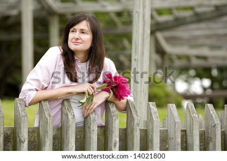 pretty woman holding flower outdoors in the summer - stock photo