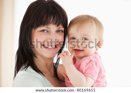 Pretty woman holding her baby in her arms while standing in the living room