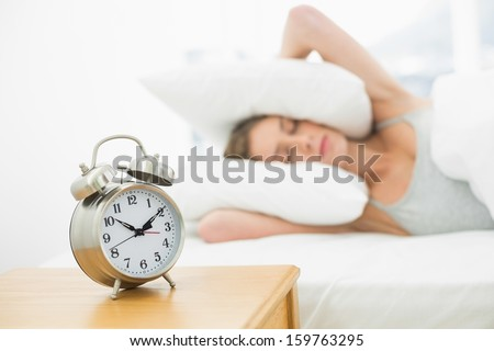 Pretty woman holding her ears closed by using pillows while lying on her bed - stock photo