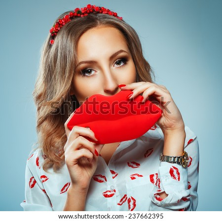 Pretty woman holding in hands big red lips, toy kiss-shaped, Valentine day concept - stock photo