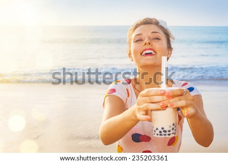 pretty woman holding modern asian beverage (bubble tea) on a beach - stock photo