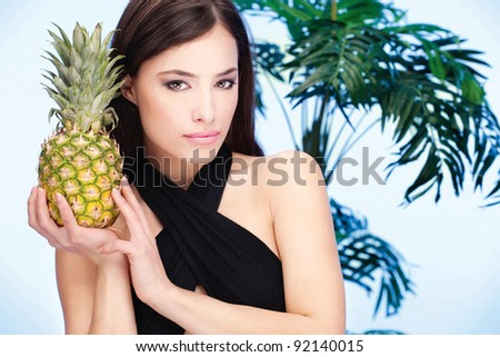 Pretty woman holding pineapple in front of a palm tree - stock photo