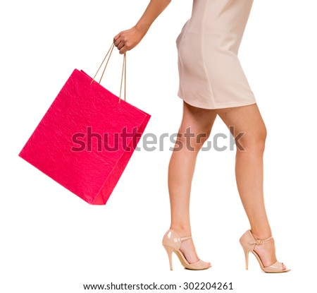 Pretty woman holding pink shopping bag on white background. Side view. Close-up.