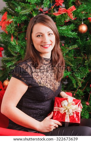 Pretty woman holding red gift box nearby Christmas tree