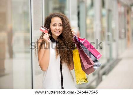 Pretty woman holding shopping bags and showing blank credit card, against mall background - stock photo