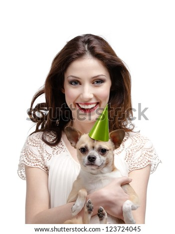 Pretty woman hugs a straw-colored small dog in cap, isolated on white