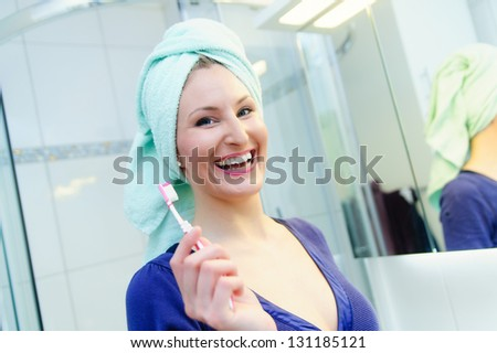 Pretty woman in a bathroom with a toothbrush - stock photo