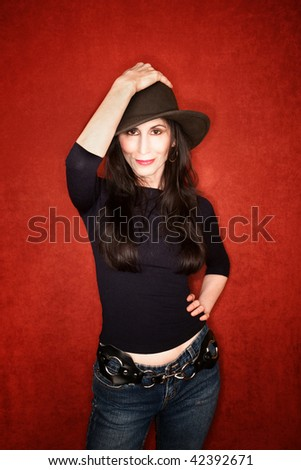Pretty woman in a dark hat and jeans - stock photo
