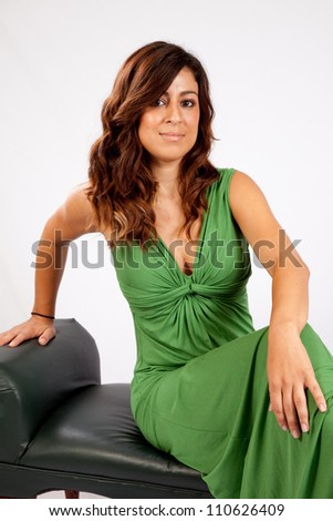 Pretty woman in a long green dress sitting on a bench and smiling at the camera with friendly pleasure - stock photo