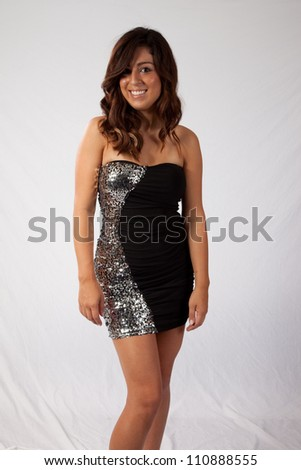 Pretty woman in a sexy little black dress,  with a happy smile for the camera - stock photo
