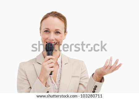 Pretty woman in a suit speaking with a microphone against white background - stock photo