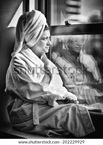 Pretty woman in bathrobe in high contrast black and white - stock photo