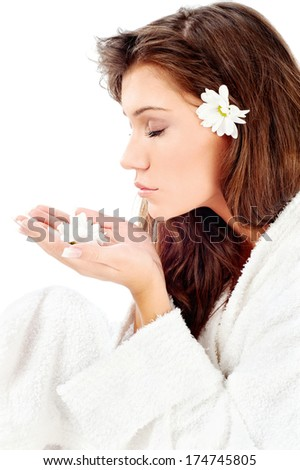 Pretty woman in bathrobe  smelling flower, isolated on white - stock photo