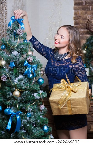 Pretty woman in blue dress decorating the fir-tree - stock photo
