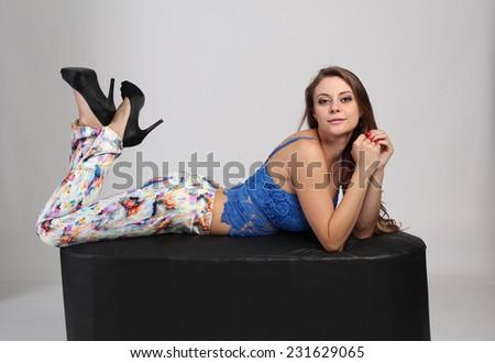 Pretty woman in blue dress lying on puff - stock photo