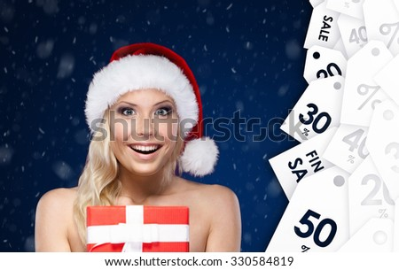 Pretty woman in Christmas cap hands present wrapped with red paper, on blue background. Winter sale - stock photo