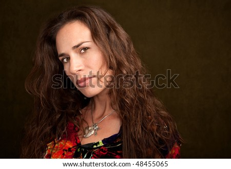 Pretty Woman in Colorful Blouse on Green Background - stock photo