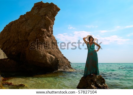 Pretty woman in dress and hat on the sea rock - stock photo