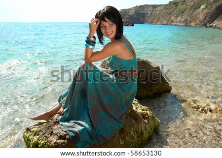 Pretty woman in dress on the sea rock - stock photo
