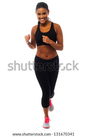 Pretty woman in fitness wear jogging towards the camera. - stock photo
