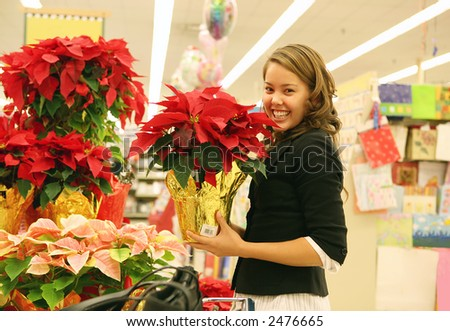Pretty woman in floral store shopping for poinsettias