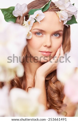 Pretty woman in floral wreath expressing calmness - stock photo