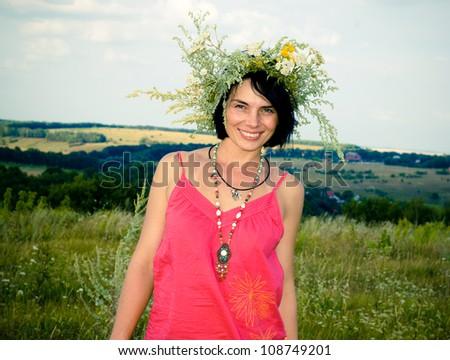 Pretty woman in flower wreath in summer field - stock photo