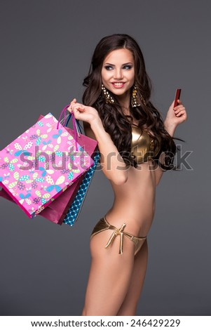 Pretty woman in gold bikini holding shopping bags and showing blank credit card, against gray background - stock photo