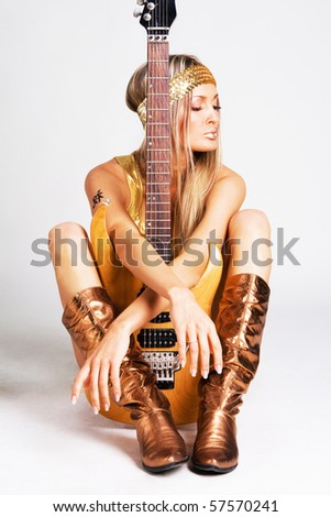Pretty woman in golden clothing holding electric guitar