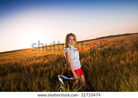 Pretty woman in golden wheat field - stock photo