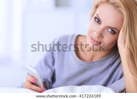Pretty woman in her living room lying on the couch sending message - stock photo