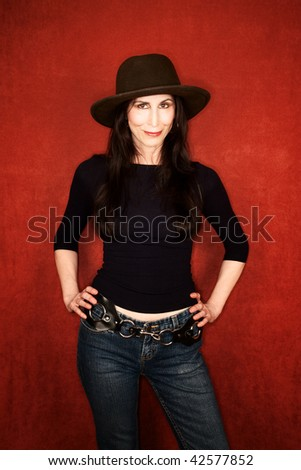 Pretty woman in jeans and a dark felt hat - stock photo