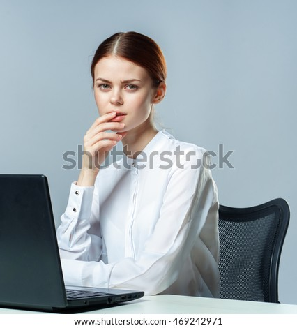 Pretty woman in office working at a laptop