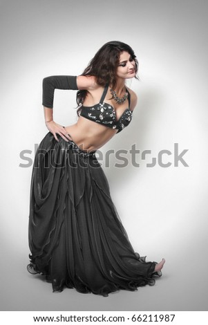 Pretty woman in oriental dancer costume, black bra and skirt. - stock photo