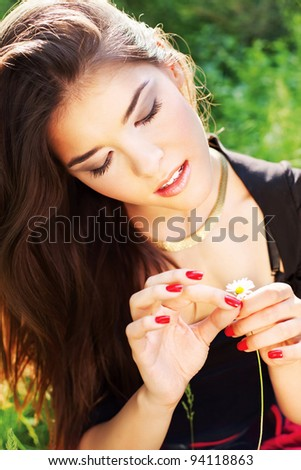 Pretty woman in park holding spring flowers, outdoor